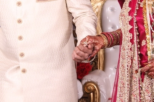 bride and groom closeup holding hands in Indian wedding