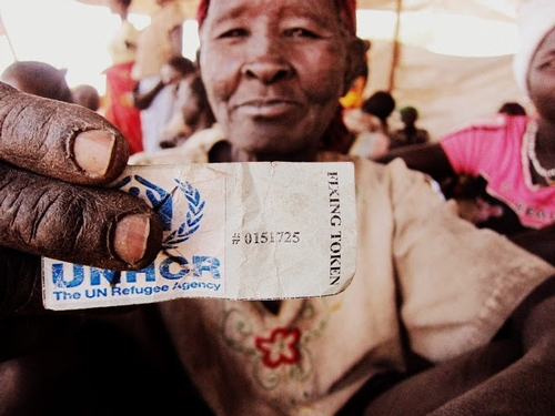 refugee holding UNHCR ticket