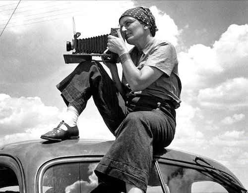 Dorothea Lange black and white self portrait showing the photographer casually dressed in trousers and kerchief perched atop a car shooting a photo with a large format camera
