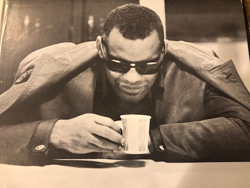 black and white old photo of Ray Charles with paper coffee cup