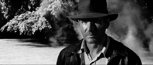 still of Harrison Ford as Indiana Jones in Raiders of the Lost Ark in black and white